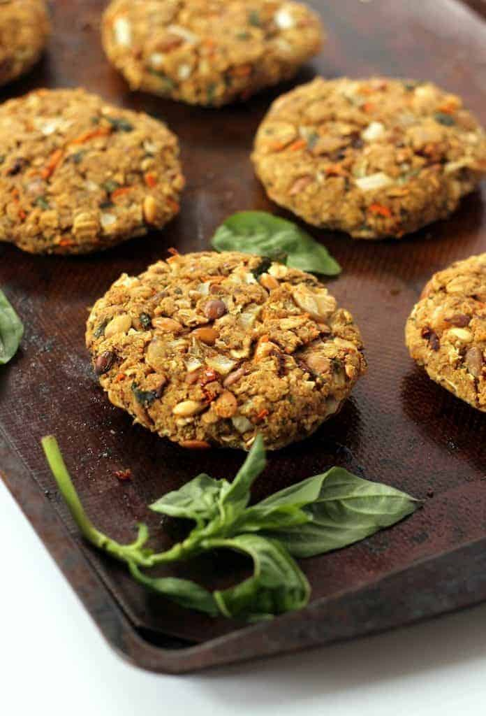 These flavorful, firm Tomato Basil Veggie Burgers are packed with protein and fiber for a tasty meal the whole family will enjoy! Vegan and gluten-free option.