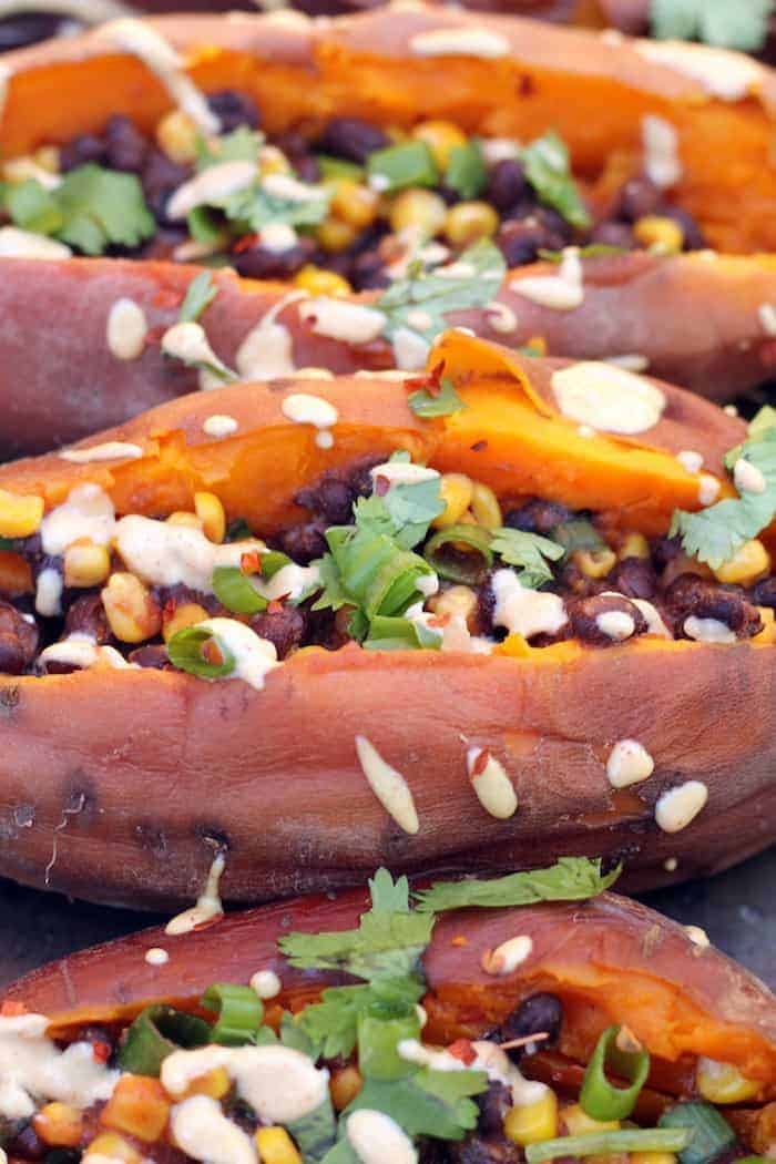 """Slow Cooker Loaded """"Baked"""" Sweet Potatoes! Cooking sweet potatoes in the slow cooker makes them extra moist and sweet! Top with black beans, corn, avocado, spices, and smoky cashew cream for an easy vegan and gluten-free meal."""