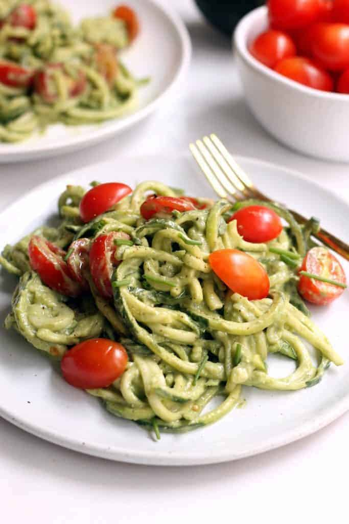 This creamy Avocado Basil Pesto Zucchini Noodles recipe makes a light and refreshing side dish any time of year! Vegan and gluten-free.