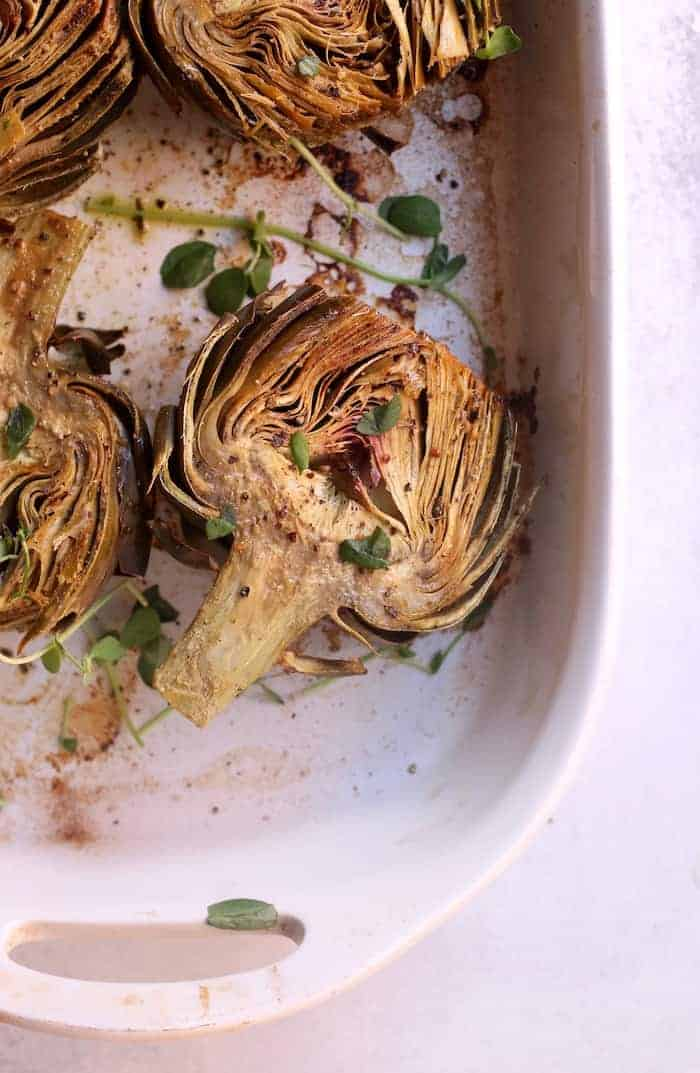 These bright and nutty oven roasted artichokes with dairy-free creamy cashew aioli make the perfect side dish or appetizer. Vegan and gluten-free.
