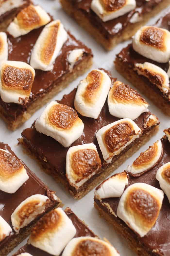 These decadent, easy S'mores Bars are made with whole grain oats, graham crackers, and cashew butter for a healthy spin on the Classic! With a rich chocolate layer and gooey marshmallows, kids and adults of all ages will adore these bars! Vegan and gluten-free option.