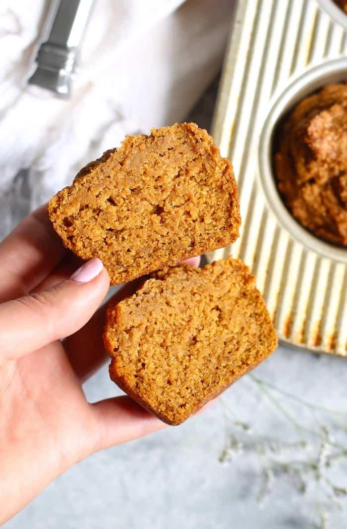hand holding cut pumpkin muffin
