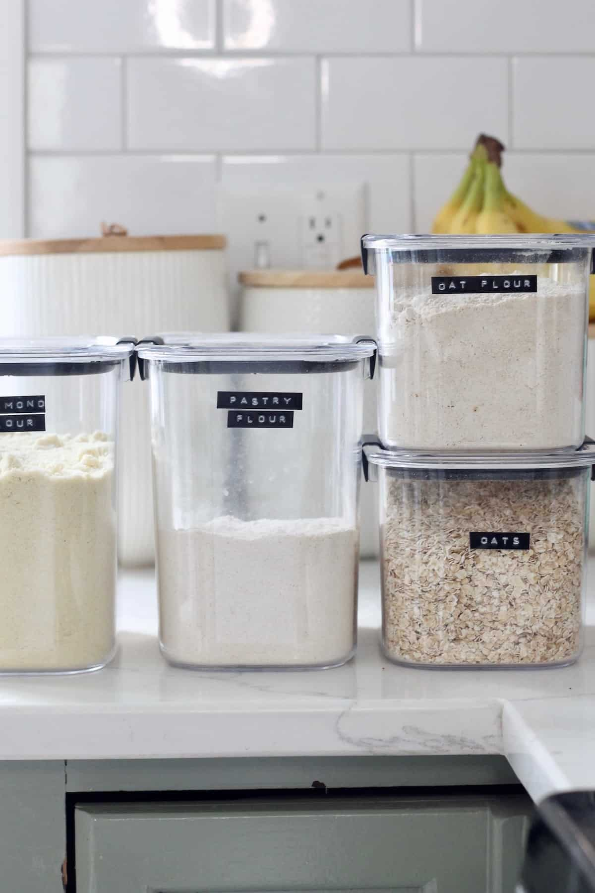 flour in containers on white counter