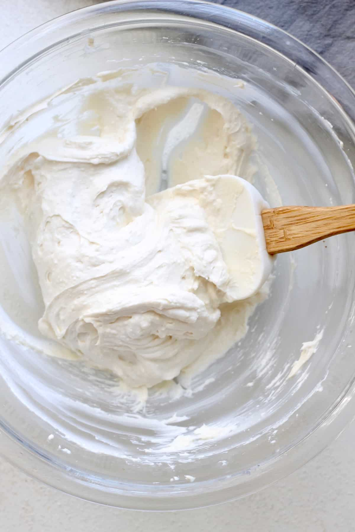 white spatula in bowl of cream cheese frosting