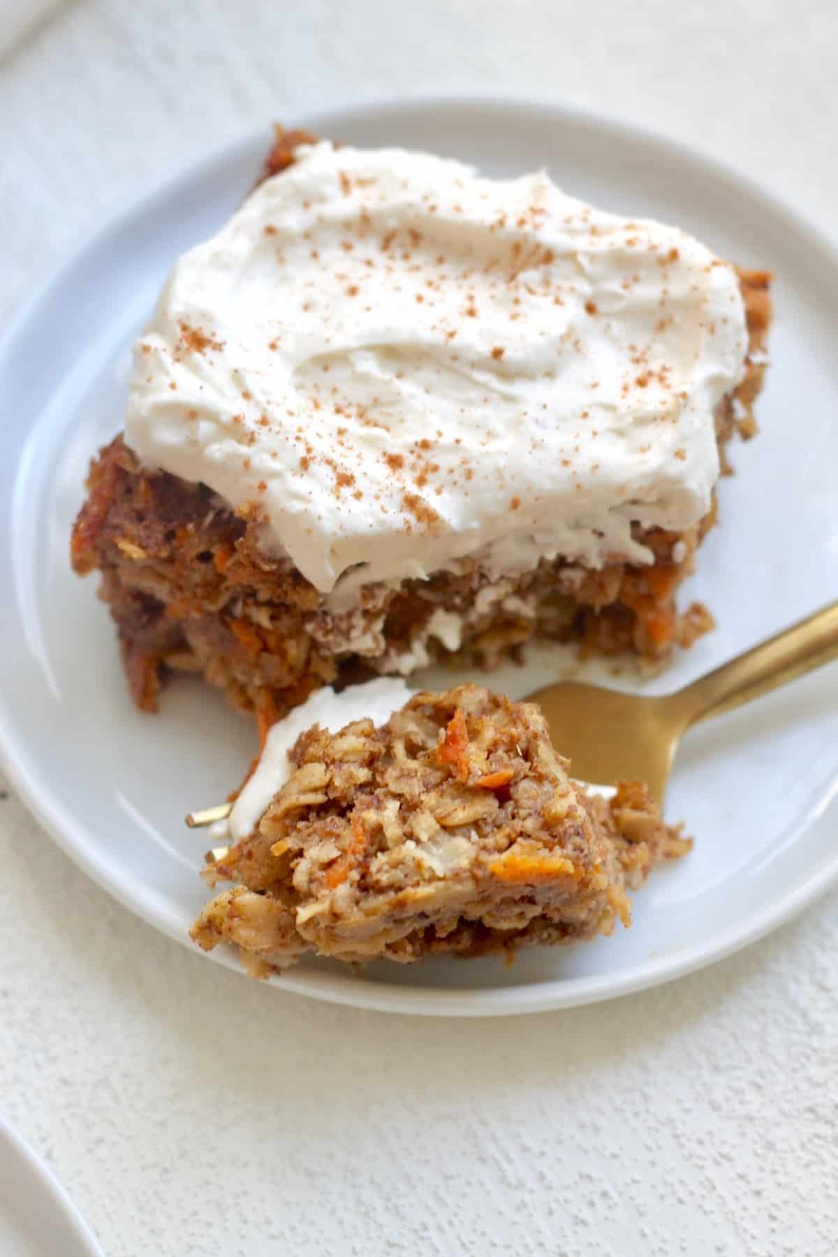 carrot cake with cream cheese frosting on plate with gold fork