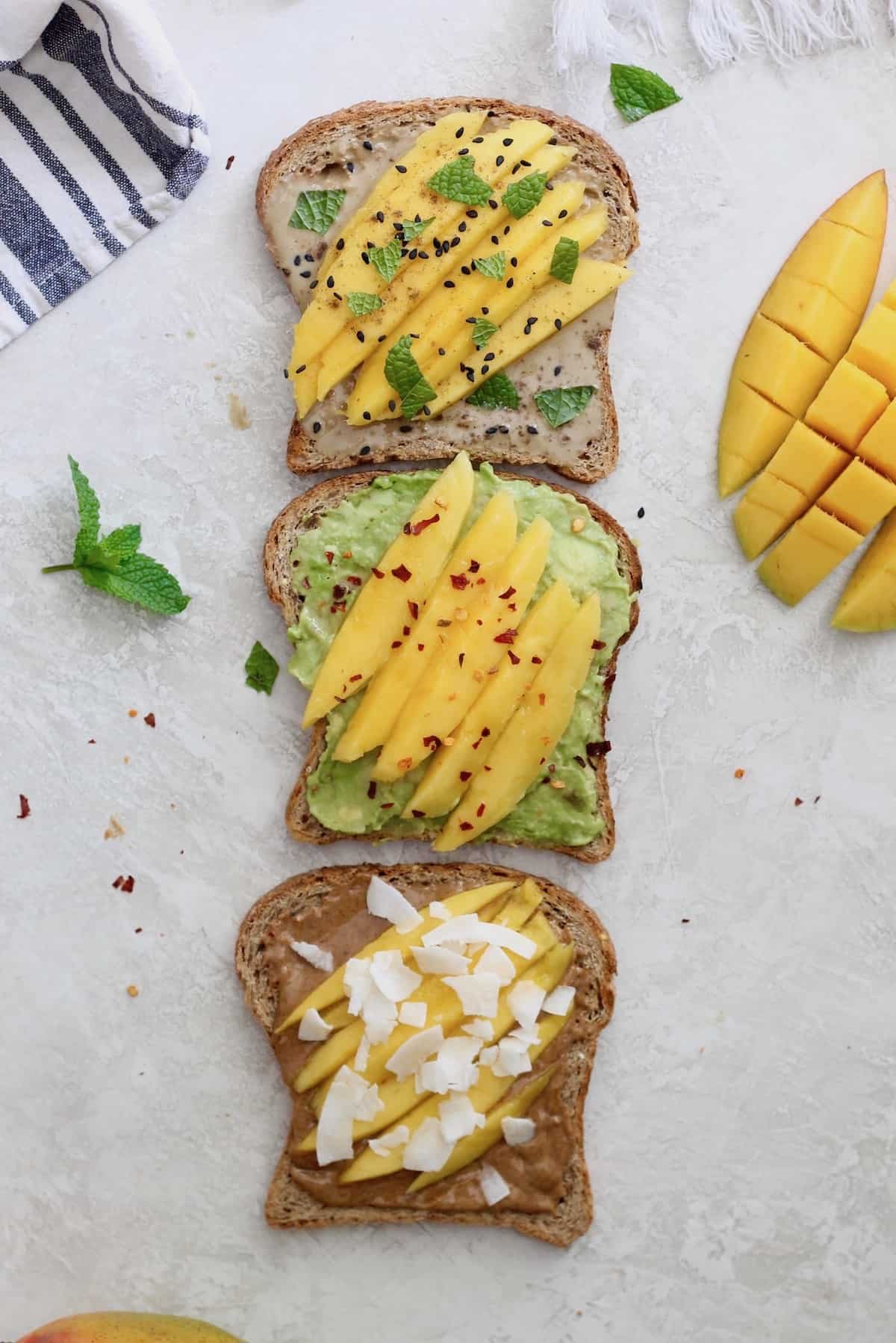 three pieces of mango toast with toppings