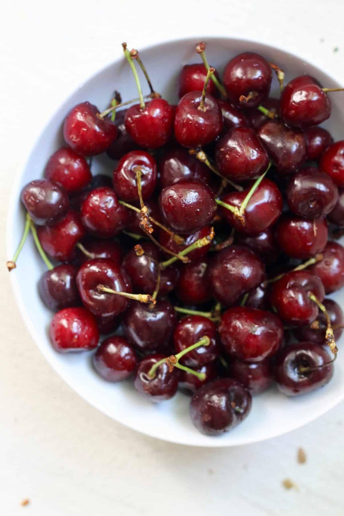 white bowl of fresh cherries