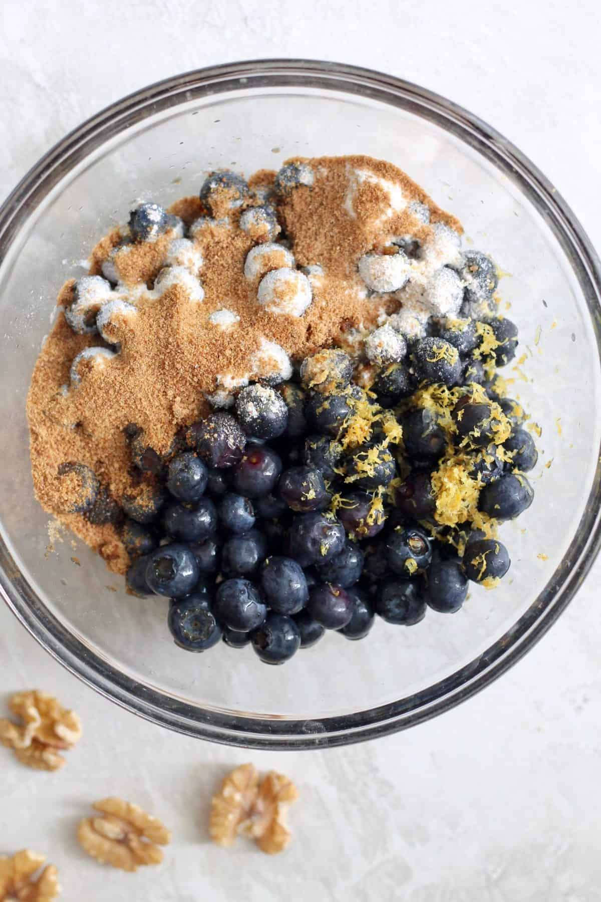 clear bowl of blueberries, flour, and sugar