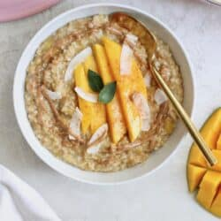 white bowl of oatmeal with mango on top