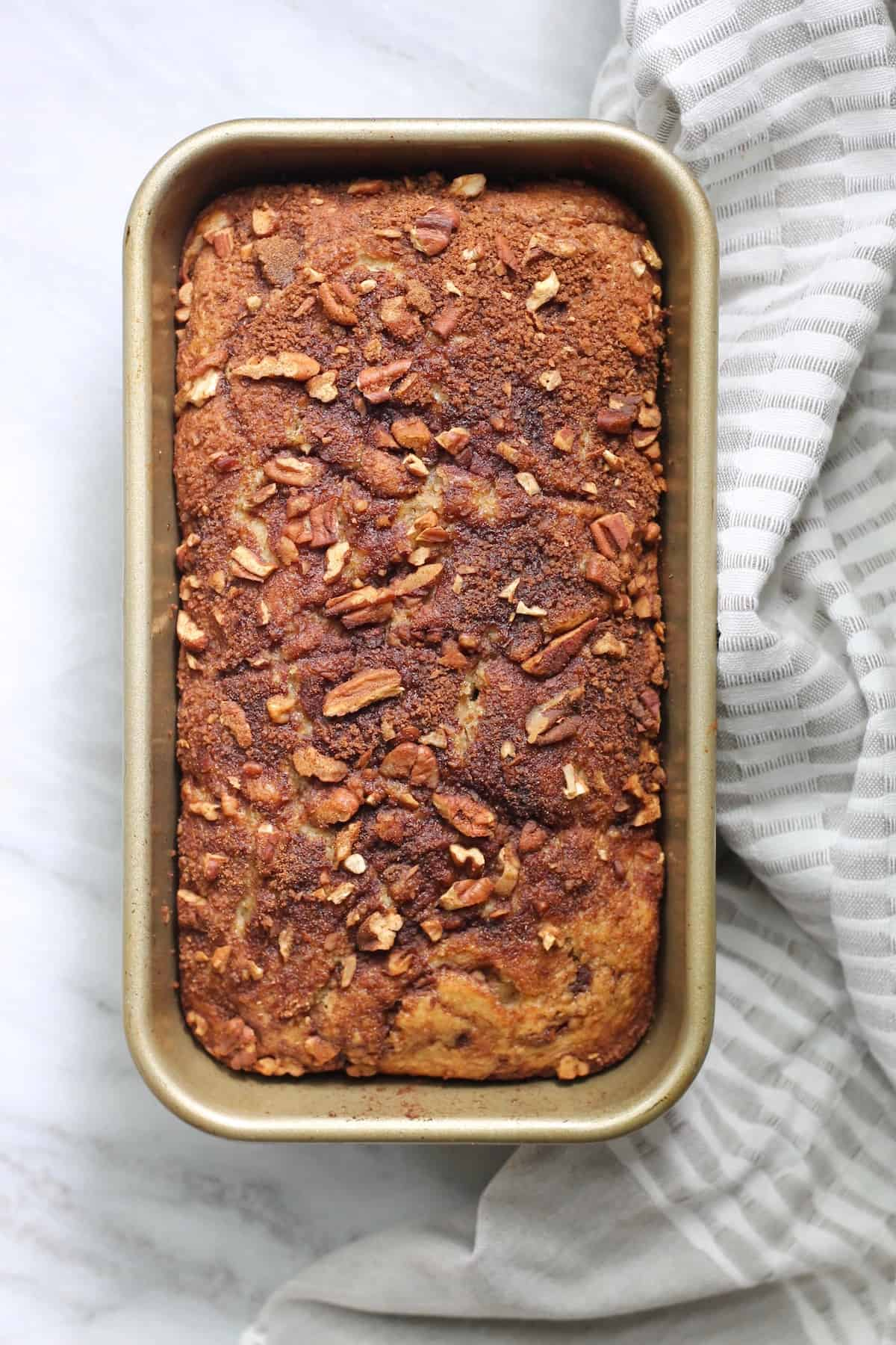 apple cinnamon loaf in gold pan with striped towel
