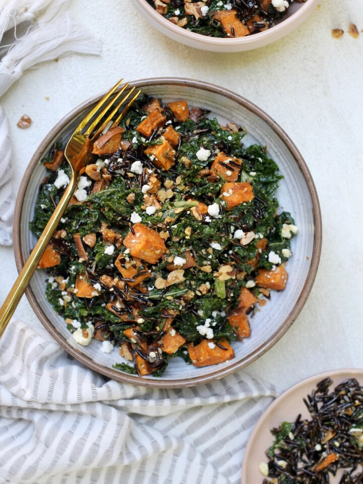 kale salad with sweet potato in bowl with gold fork