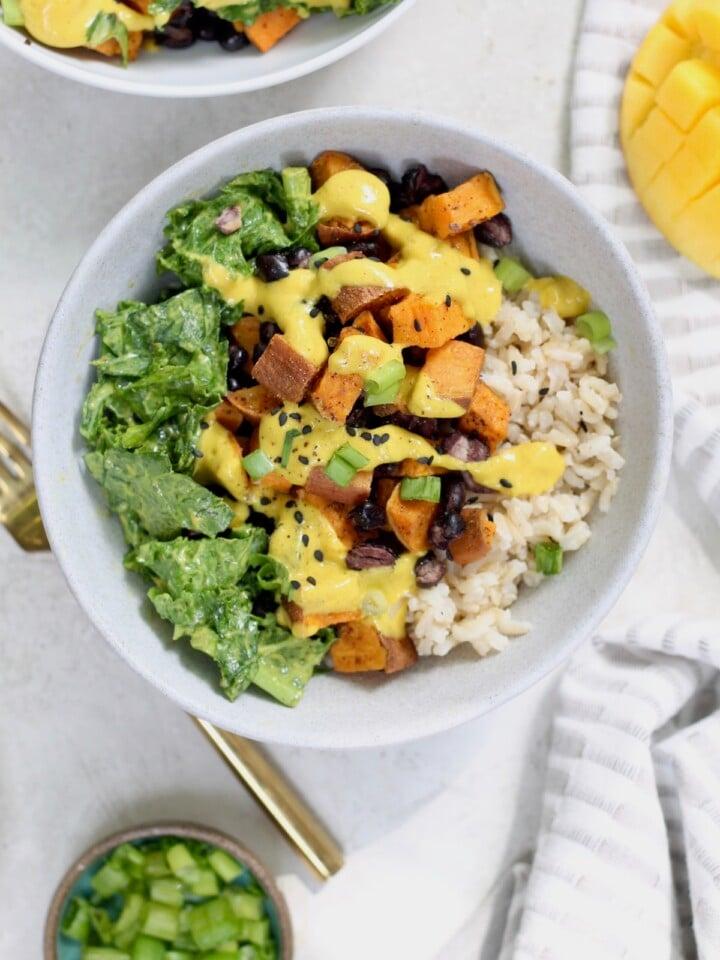bowl with rice, kale, sweet potato, and mango sauce