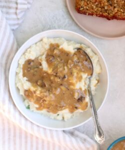 white bowl of gravy with silver spoon
