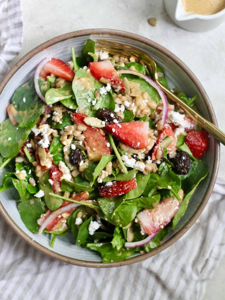 bowl of strawberry spinach salad with fork and dressing