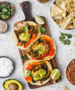 wood cutting board with three veggie fajitas and toppings