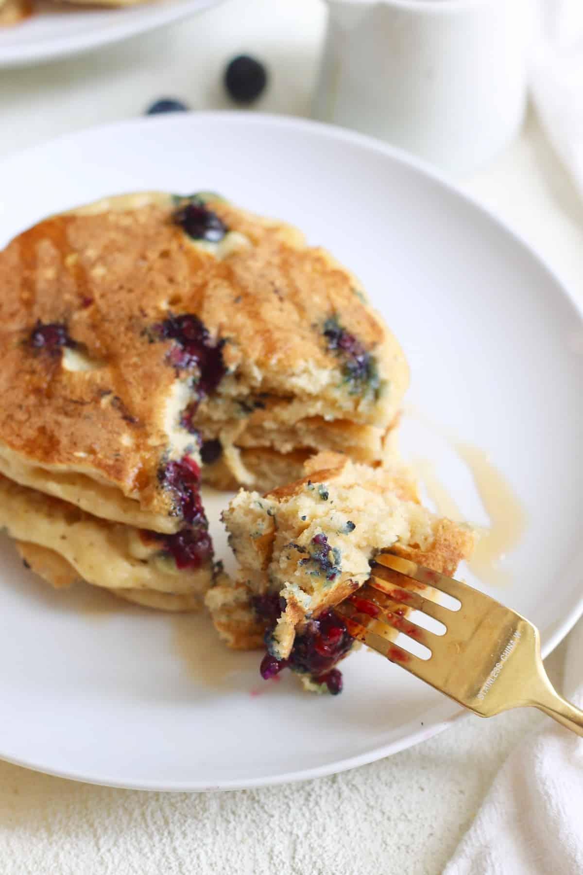 gold fork taking bite of lemon blueberry pancakes
